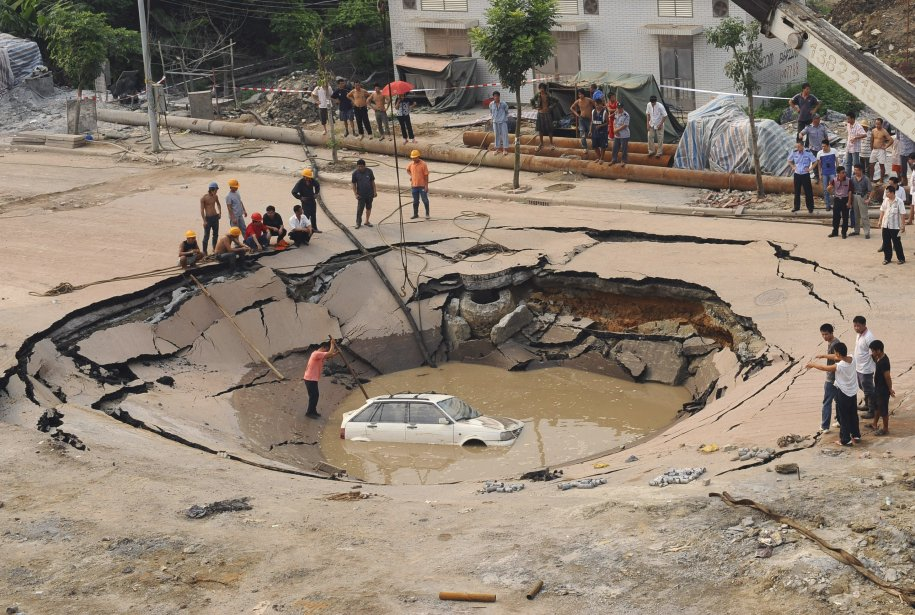 in-september-2008-a-road-collapsed-into-a-16-foot-deep-50-foot-wide-hole-and-trapped-a-car-in-the-guangdong-province-of-china